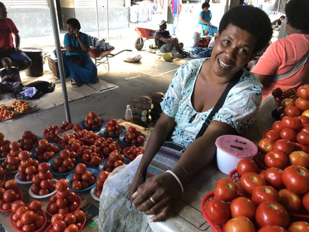 マーケットでトマトを売っている女性